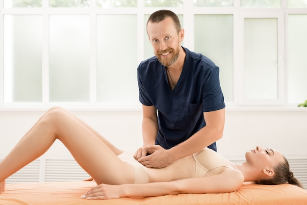 女性患者の腹部をマッサージする成人男性オステオパシー手技療法士