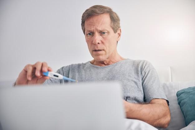 그의 침실에 앉아 노트북을 사용하는 동안 의사와 온라인 상담을하는 성인 남성 사람