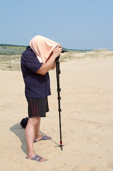 Adult male photographer with a towel on his head from the heat is taking pictures with a camera on a stand in the desert