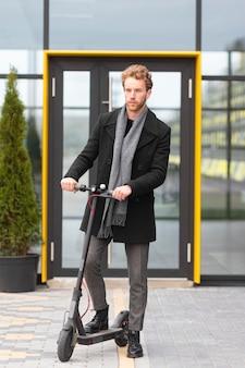 Maschio adulto in posa con uno scooter elettrico