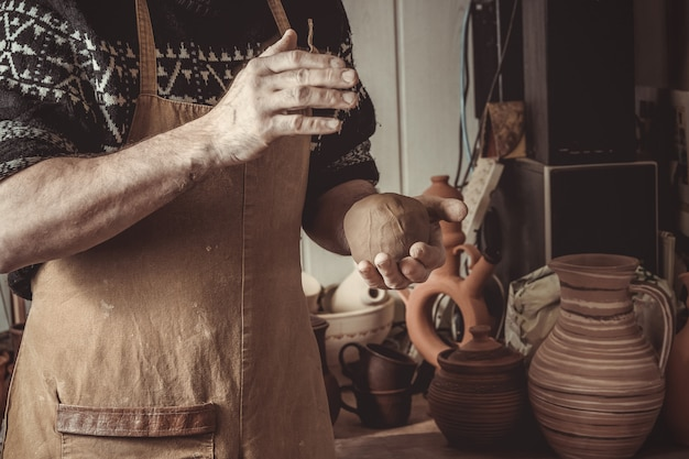 Adult male potter master mashing the clay