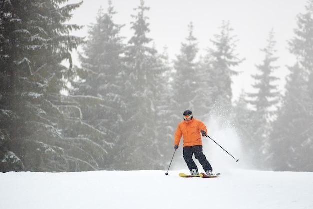 Взрослый мужчина катается на лыжах во время сильного снегопада. монохромный вид. активный отдых на природе, спортивный отдых, отдых в уединении