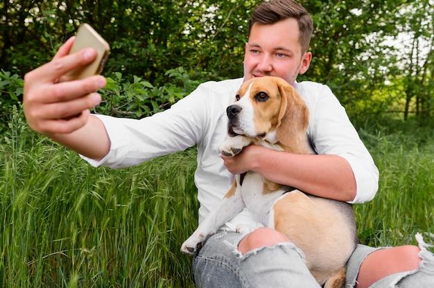 彼の犬と一緒にselfieを取る大人の男性