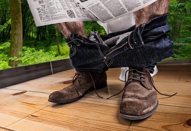 Adult male wearing jeans and shoes reading newspaper while sitting on the toilet seat