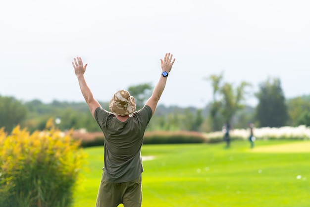 Взрослый мужчина в шляпе и зеленой рубашке держит руки вверх, чтобы сигнализировать другим, идущим на размытом фоне