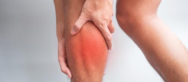 灰色の背景に彼の筋肉痛を持つ成人男性。ふくらはぎの筋肉が引っ張られて脚が痛む老人。スポーツ傷害と医療概念