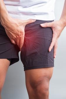 ランニング中に筋肉痛のある成人男性。ランナーは、鼠径部の引っ張り、腸脛靭帯症候群(itbs)、または前立腺癌による脚の痛みがあります。スポーツ傷害と医療概念