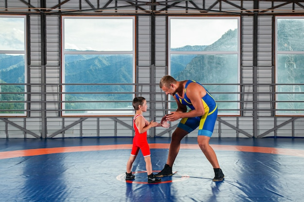 An adult male wrestler coach teaches the basics of wrestling and sets up a little boy to compete.