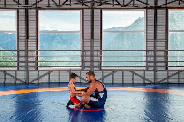 An adult male wrestler coach teaches the basics of wrestling