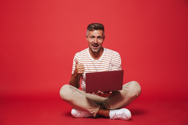 縞模様のtシャツを着た30代の成人男性が笑顔で灰色のラップトップを使用して、床に座って足を組んで赤で隔離