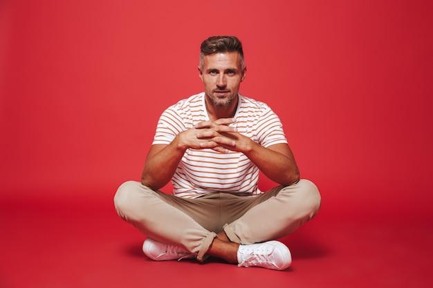 赤で隔離された足を組んで床に座って笑っているストライプのtシャツの30代の成人男性
