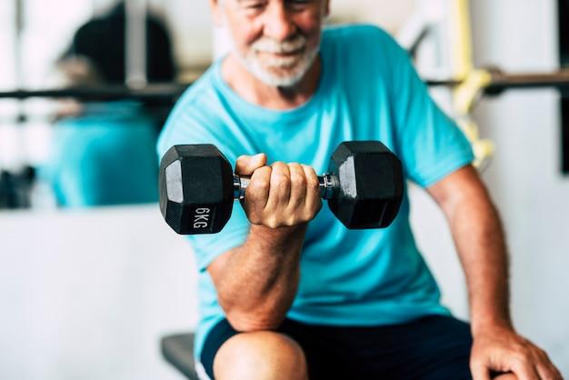 ダンベルで体を動かしているジムの成人男性と成熟した先輩-ベンチに座って屋内でハピートレーニングをしている男性