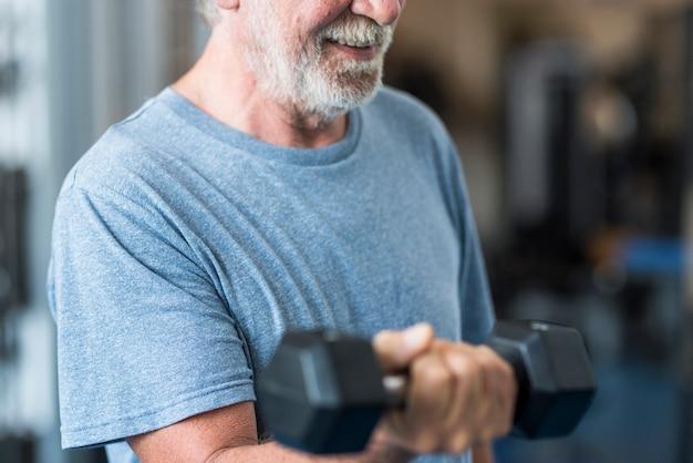 ダンベルで体を動かすジムの成人男性と成熟した先輩-屋内での一人の男性のハピートレーニング