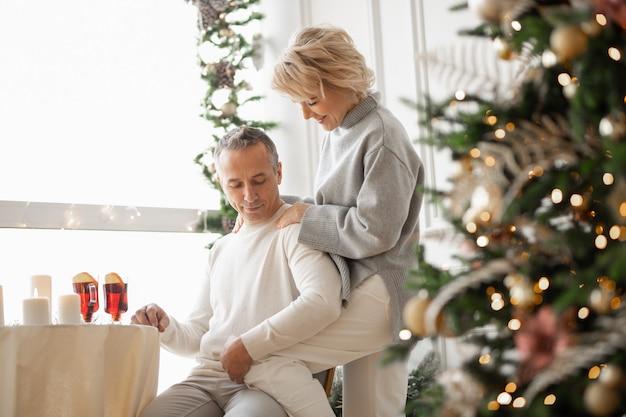 クリスマスツリーとホールのお祝いのテーブルの近くで抱き締める大人の男性と女性