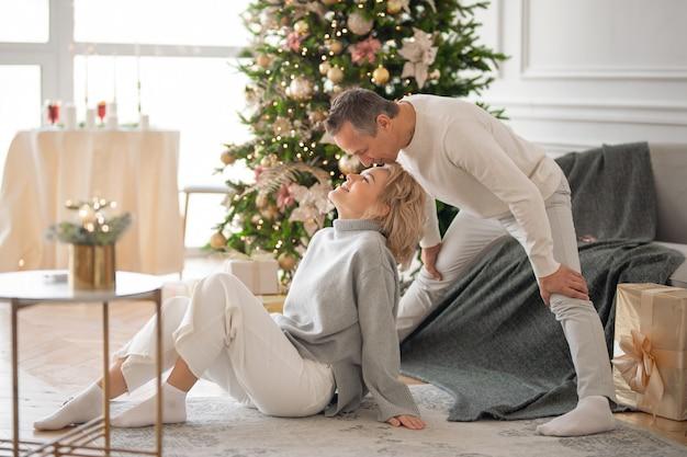 大人の男性と女性がクリスマスツリーの近くに座ってキスします
