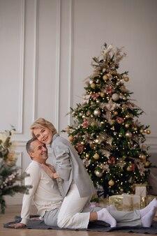 Взрослый мужчина и женщина сидят на полу возле елки и обнимаются