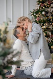 Взрослые мужчина и женщина сидят на полу возле елки и обнимаются