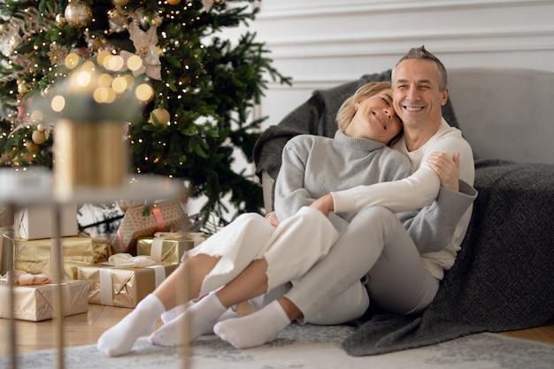 大人の男性と女性がソファの近くの床に座って抱きしめます