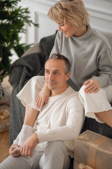 Взрослый мужчина и женщина сидят на диване возле елки и обнимаются