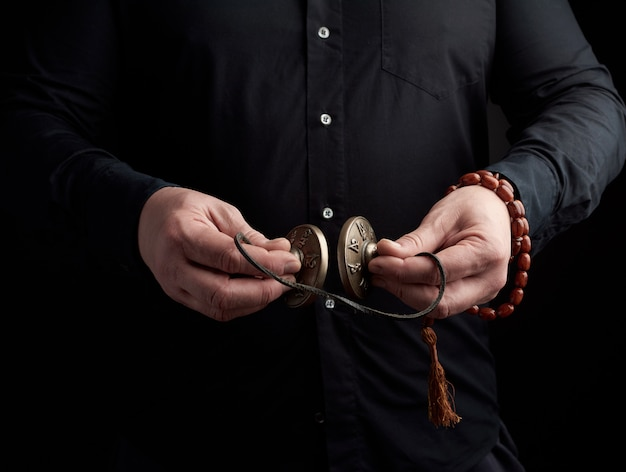 Adult man in black clothes holds in his hands a pair of bronze karatal on a leather rope