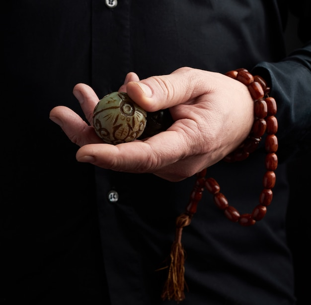 Adult man in black clothes holds in his hands a stone magic ball