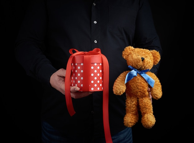 Adult man in a black shirt holds a blue square box tied with a red ribbon and brown teddy bear, concept of congratulations