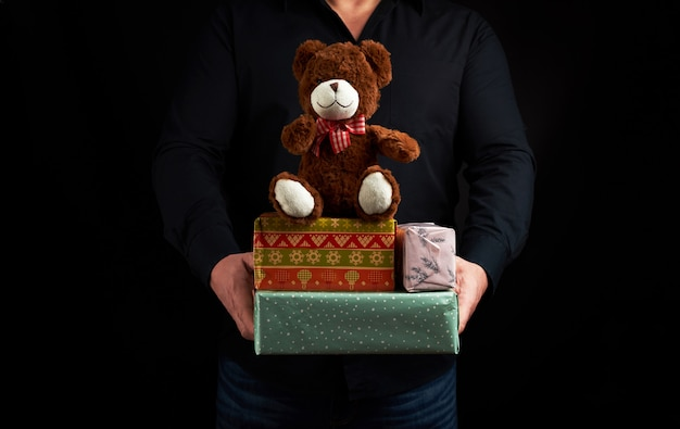 Adult man in a black shirt holds a blue square box tied with a red ribbon and brown teddy bear