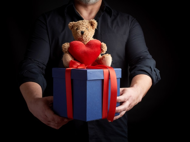 An adult man in a black shirt holds a blue square box tied with a red ribbon and sits on top of a brown teddy bear with a heart