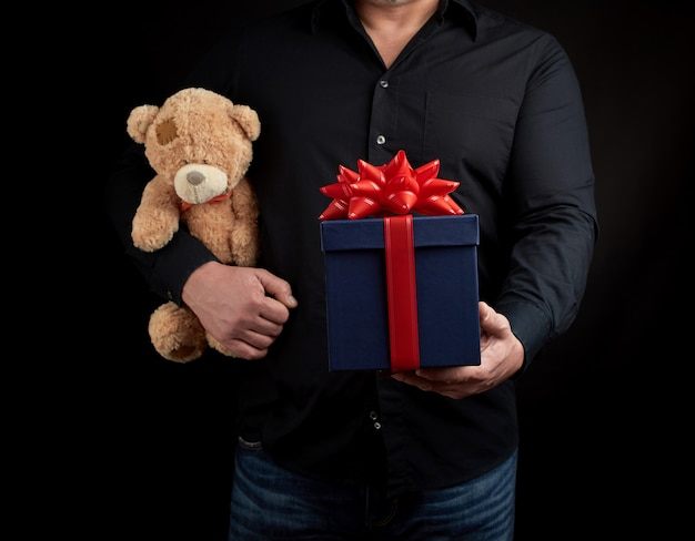 Adult man in a black shirt holds a blue square box tied with a red ribbonnd brown teddy bear