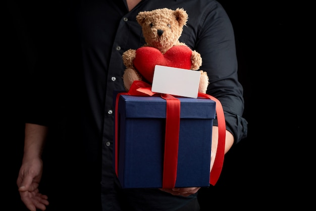 Adult man in a black shirt holds a blue square box tied with a red ribbonnd sits on top of a brown teddy bear