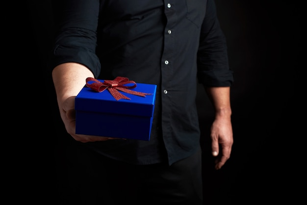 Adult man in a black shirt holds a blue square box with a red bow tied on a dark background