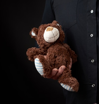 Adult man in a black shirt holds a brown teddy bear on dark
