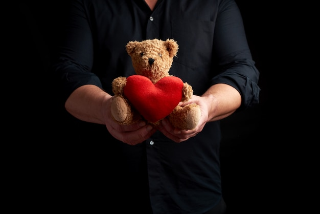 Adult man in a black shirt holds a brown teddy bear with a red heart on a dark background