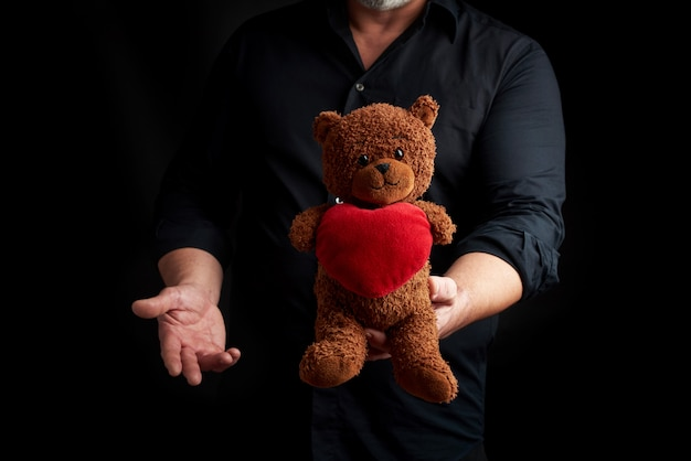 Adult man in a black shirt holds a brown teddy bear with a red heart