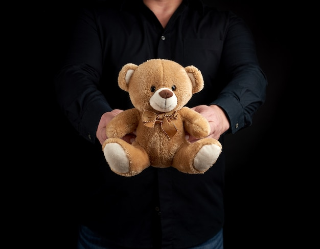 Adult man in a black shirt holds a brown teddy bear