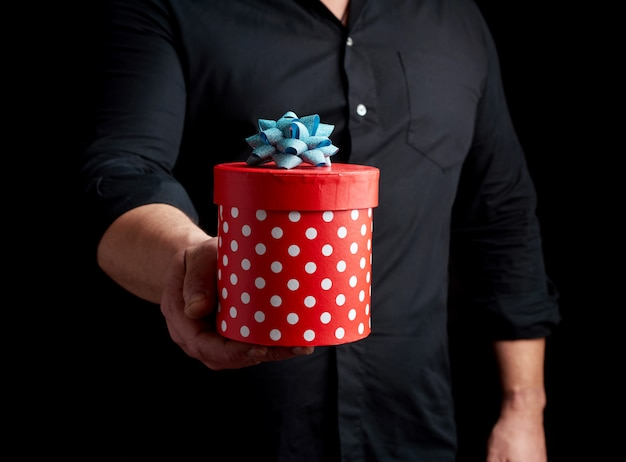 Adult man in a black shirt holds in his hand a round red box of polka dots with a blue bow