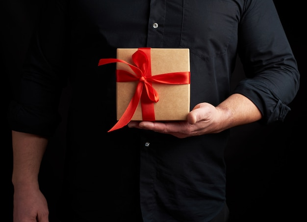 Adult man in a black shirt holds in his hand a square brown boxlet tied with a red ribbon