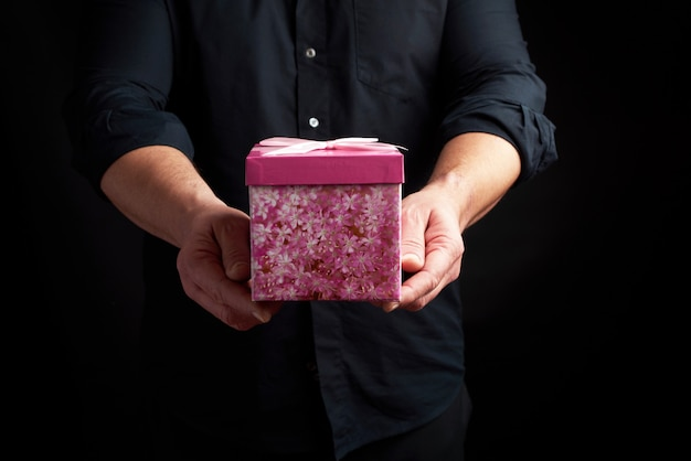 Adult man in a black shirt holds a pink square box with a bow