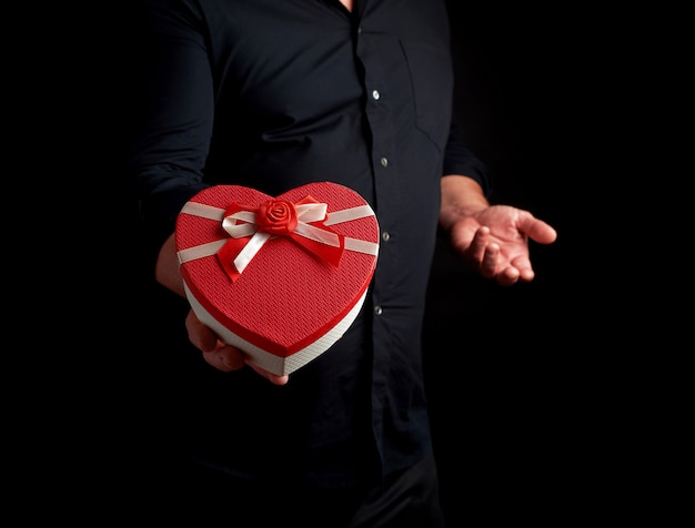 Adult man in a black shirt holds a red cardboard box in the form of a heart with a bow on a dark background