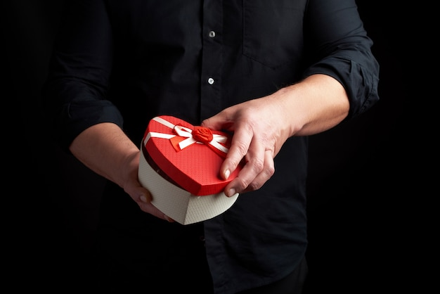 Adult man in a black shirt holds a red cardboard box in the form of a heart with a bow