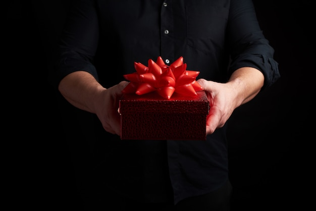 Adult man in a black shirt holds a red square box with a knotted bow on a dark background