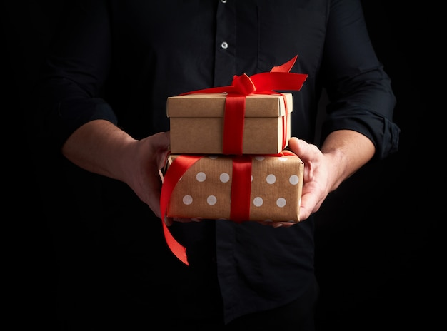Adult man in a black shirt holds a stack of gifts wrapped in brown paper with a red bow