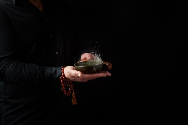 Adult man in a black shirt rotates a wooden stick around a copper tibetan bowl of water