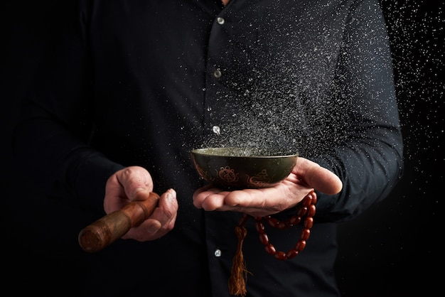 Adult man in a black shirt rotates a wooden stick around a copper tibetan bowl with water