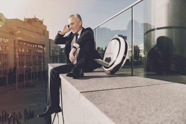 Adult man in a black suit talking on the phone