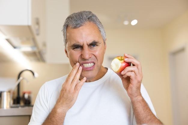 大人の男がリンゴを噛んだときに歯を折った