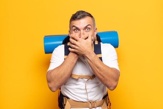 Взрослый мужчина прикрывает рот руками с шокированным, удивленным выражением лица, хранит секрет или говорит: ой