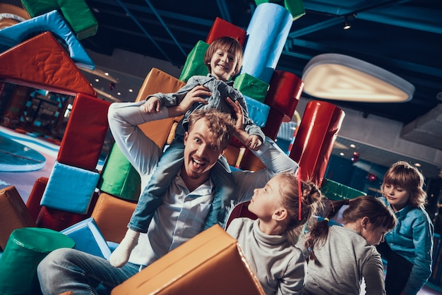 Adult man and cute children on indoor playground