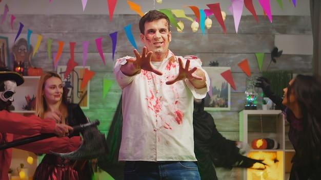 Взрослый мужчина замаскированный под страшного зомби с профессиональным макияжем на вечеринке в честь хэллоуина со своими друзьями в украшенном доме.
