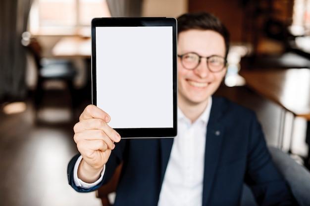 スーツを着た大人の男性が、コーヒーショップに座って笑顔で画面を見せている顔の前にタブレットを持っています。